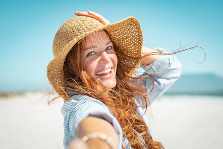 Foto de Portrait of beautiful mature woman in casual wearing straw hat in sunny warm day at seaside.Cheerful young woman smiling at beach during summer vacation. Happy girl with red hair and freckles enjoying the sun. - Imagen libre de derechos