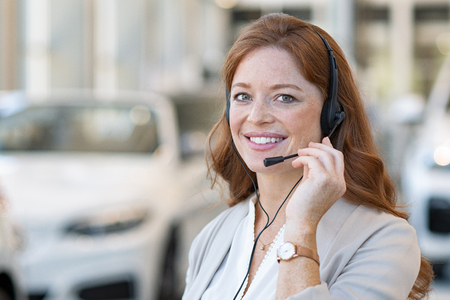 Photo for Beautiful female customer support wearing headset and looking at camera. Portrait of smiling woman customer service representative working with cars in background. Young call center operator at car rental office. - Royalty Free Image
