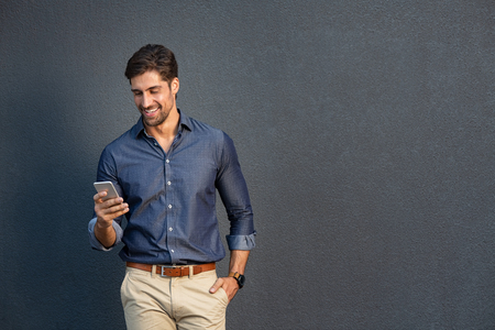 Photo for Portrait of young man leaning against a grey wall using mobile phone. Happy business man messaging with smartphone isolated on gray background with copy space. Smiling casual guy typing and reading a message on cellphone leaning on wall. - Royalty Free Image