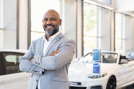 Photo for Smiling businessman standing with arms crossed at new car showroom. Confident senior car dealer standing in dealership while looking at camera. Portrait of professional black salesman in luxury auto showroom. - Royalty Free Image