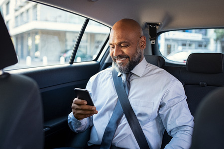 Photo pour Successful african businessman working on phone smiling witting in car. Portrait of mature smiling business man in formal clothes using smartphone while sitting on back seat of luxury business car. Senior formal man reading confirmation mail on smartphone and smiling in a taxi. - image libre de droit