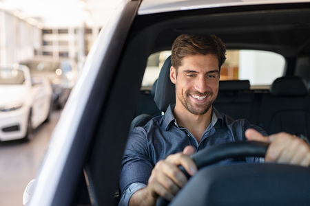 Photo pour Young smiling man examining a new car in a showroom. Happy guy feeling comfortable sitting on driver seat in his new car at showroom. Man ready to make first test drive. - image libre de droit