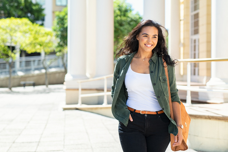 Photo pour Pretty casual natural woman walking in urban street and looking away. Cheerful latin girl with bag travelling across the city. Beautiful young woman smiling outdoor. - image libre de droit