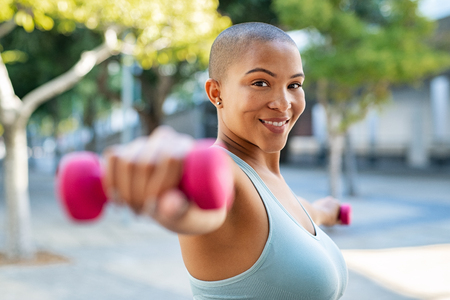 Foto de Portrait of happy bald woman exercising while looking at camera. Smiling girl doing sports outdoors with dumbbells lifting weights. Fit fitness girl in sportswear exercising outside to slim down. - Imagen libre de derechos