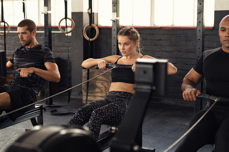 Foto de Young man and beautiful woman working out with rowing machine at crossfit gym. Athletic class doing exercise with rowing machine. Group of fitness concentrated people in sportswear training. - Imagen libre de derechos