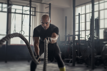 Foto de Athlete working out with battle rope at gym. Bald african man training using battle ropes. Fit sportsman doing crossfit exercise in an industrial dark gym. - Imagen libre de derechos