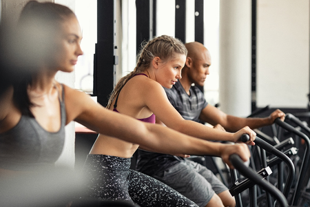 Photo pour Group of determined multiethnic people at gym exercising on stationary bike. Concentrated fitness woman training on exercise bike with class. Man and women behind riding cycling machine in hard efforts at gym. - image libre de droit