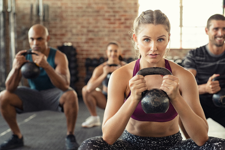 Foto de Group of fit people holding kettle bell during squatting exercise at crossfit gym. Fitness girl and men lifting kettlebell during strength training exercising. Group of young people doing squat with kettle bell. - Imagen libre de derechos