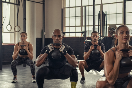 Photo pour Fitness women and determined men exercising with kettlebell at crossfit gym. Group of young people doing a kettle bell exercise along with squatting. Multiethnic group of fit class doing crouch exercise while holding weight. - image libre de droit