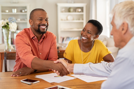 Foto de Mature black husband shaking hands with senior agent on taking loan. Happy african couple sealing with handshake a contract with financial advisor for investment. Man making sale purchase deal concluding with a handshake with estate agent. - Imagen libre de derechos