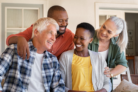 Photo pour Cheerful friends sitting in courtyard enjoying the afternoon together. Group of four mature people sitting outside home and laughing. Happy senior man and old woman enjoying with mature african couple. - image libre de droit