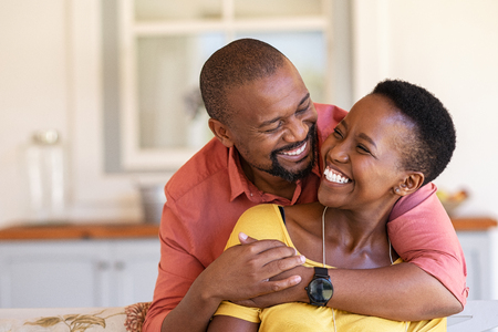 Foto de Mature black couple embracing on sofa while looking to each other. Romantic black man embracing woman from behind while laughing together. Happy african wife and husband loving in perfect harmony. - Imagen libre de derechos