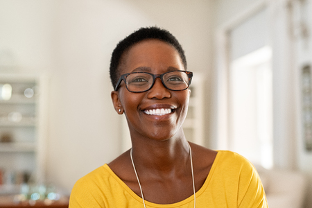 Foto de Portrait of young woman at home wearing spectacles. Beautiful mature woman wearing eyeglasses and looking at camera. Cheerful african american lady with glasses and short hair. - Imagen libre de derechos