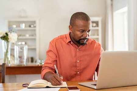 Foto de Mature man working on laptop while taking notes. Businessman working at home with computer while writing on agenda. African man managing home finance, reviewing bank account and using laptop in living room. - Imagen libre de derechos