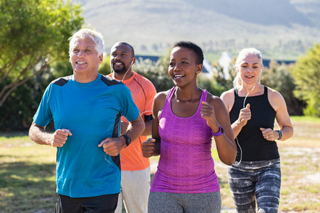 Foto de Healthy group of mature people jogging on track at park. Happy senior couple running at park with african friends. Multiethnic middle aged friends exercising together outdoor. - Imagen libre de derechos