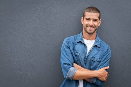 Photo for Portrait of handsome young man in casual denim shirt keeping arms crossed and smiling while standing against grey background. Stylish and confident guy leaning against gray wall with copy space. Cheerful friendly man laughing and looking at camera. - Royalty Free Image