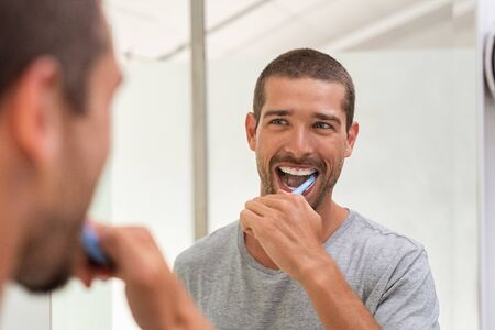 Photo pour Smiling young man with toothbrush cleaning teeth and looking mirror in the bathroom. Handsome young man brushing his teeth in morning in bathroom. Happy guy in pajamas brushing teeth at night before going to sleep. - image libre de droit