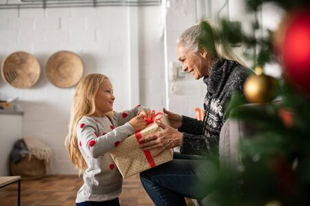 Foto de Happy senior woman giving christmas surprise to little girl at home. Excited granddaughter unpacking present under christams tree with old granny in sweater. Grandmother giving xmas gift to grandchild. - Imagen libre de derechos