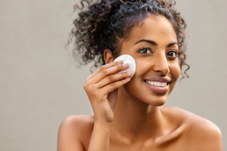 Foto de Young pretty african american woman taking off her makeup with cotton wipe sponge. Smiling girl cleaning face with cotton pad isolated over background. Black young woman cleansing face, daily healthy beauty routine. - Imagen libre de derechos