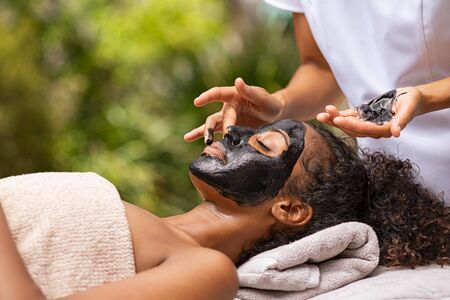 Photo pour African young woman resting with eyes closed in spa while masseuse applying charcoal face mask. Girl relaxing in spa with black mud on face for beauty treatment. Beautician applying peeling mask on face. - image libre de droit