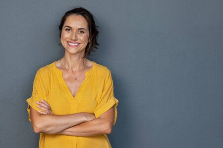 Photo pour Confident mature woman with crossed arms in casual clothing standing against grey background with copy space. Successful smiling woman with toothy smile looking at camera. Beautiful positive businesswoman standing. - image libre de droit