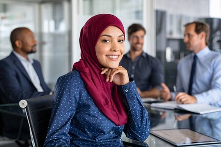 Foto de Beautiful arab businesswoman looking at camera and smiling while working in office. Portrait of cheerful islamic young woman wearing hijab at meeting. Muslim business woman working and sitting at conference table with multiethnic colleagues in background. - Imagen libre de derechos