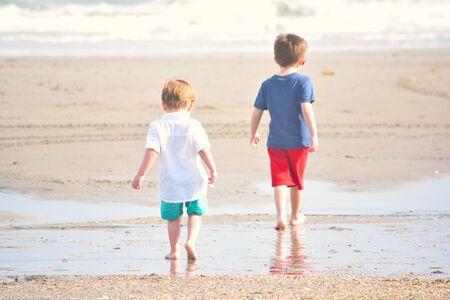 Younger Brother Follows Boy Along Ocean Shore