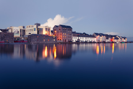 Foto de Buildings on the bank of the river during High tide in the city in dusk. Claddach, Galway, Ireland. - Imagen libre de derechos