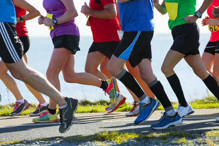 Photo pour Group of runners compete in the race on coastal road - image libre de droit