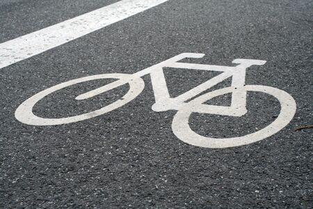 white painted sign on the asphalt for bike path