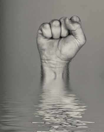 Foto de Mans Fist comes out of the water with reflection - Imagen libre de derechos