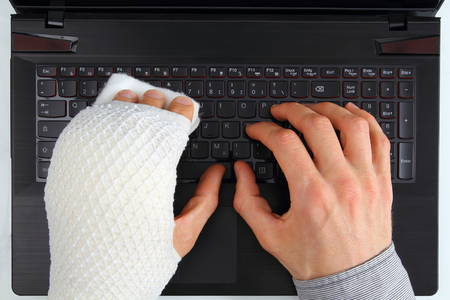 Photo pour Working on a notebook with hand injury - image libre de droit