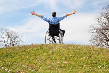 Foto de Happy Wheelchair user on a green hill - Imagen libre de derechos