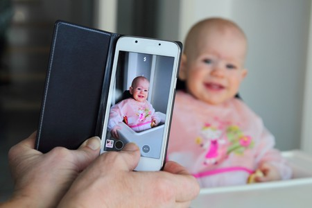 Foto de Taking a picture of a eating baby with a mobile phone - Imagen libre de derechos