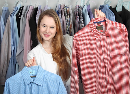 Foto de A Employee of a dry cleaning presenting two clean shirts - Imagen libre de derechos