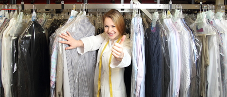 Photo for A Woman in dry cleaning betwee shirts with thumb up - Royalty Free Image