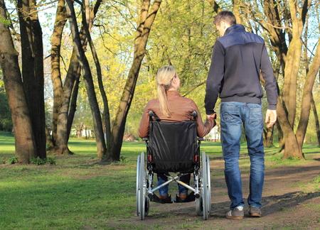 Foto de A Lovers couple in wheelchair and not handicapped - Imagen libre de derechos