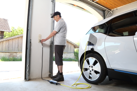 Photo pour A Man Charging Electric car  at outlet at home - image libre de droit