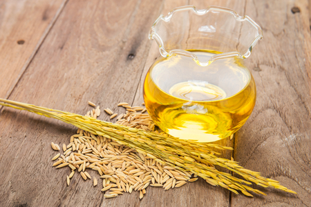 Foto de Rice bran oil in bottle glass and unmilled rice on wooden background - Imagen libre de derechos