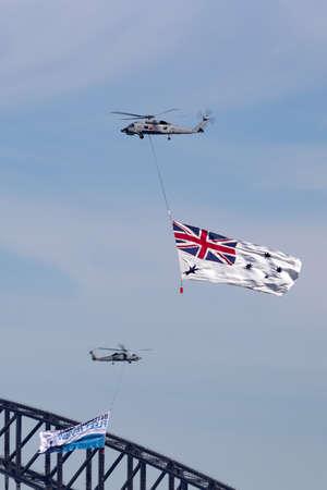 Foto de Sydney, Australia - October 5, 2013: Royal Australian Navy (RAN) Sikorsky S-70B-2 Seahawk Helicopter N24-001 flying the White Ensign of the RAN over Sydney Harbour. - Imagen libre de derechos