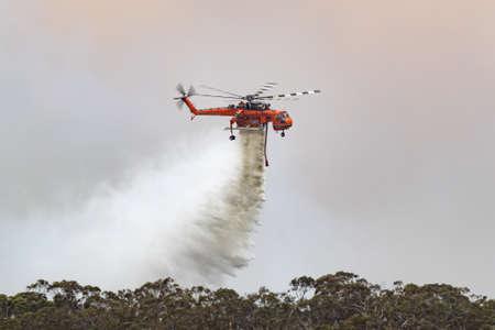 Foto de Bundoora, Australia - December 30, 2019: Erickson Air Crane helicopter dropping a large load of water onto a bushfire. - Imagen libre de derechos