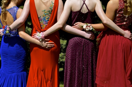 Photo for Girls in colorful gowns and hand corsages are ready for prom night - Royalty Free Image