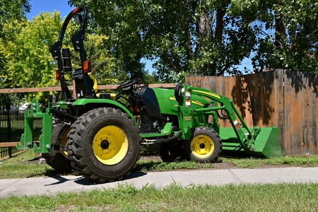 Photo pour MOORHEAD, MINNESOTA, July 9, 2018: The new 2520 green tractor assisting in fence repair is a product of John Deere Co, an American corporation that manufactures agricultural, construction, forestry machinery, diesel engines, and drivetrains - image libre de droit