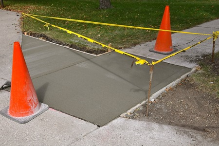 Photo pour Cones and yellow caution ribbon surround a finished repair project on a sidewalk and driveway. - image libre de droit