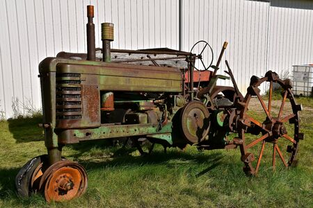 Foto de VERGAS, MINNESOTA, October 6, 2019: The old John Deere tractor missing a front tire is a  product of John Deere Co, an American corporation that manufactures agricultural and construction equipment, drive trains, and transmission. - Imagen libre de derechos