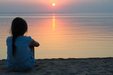 Foto de girl sitting on the beach in a light summer dress, watching the sun set into the sea on the horizon - Imagen libre de derechos