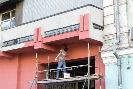 Photo pour in jeans and a work shirt facade paint roller standing on the scaffolding - image libre de droit