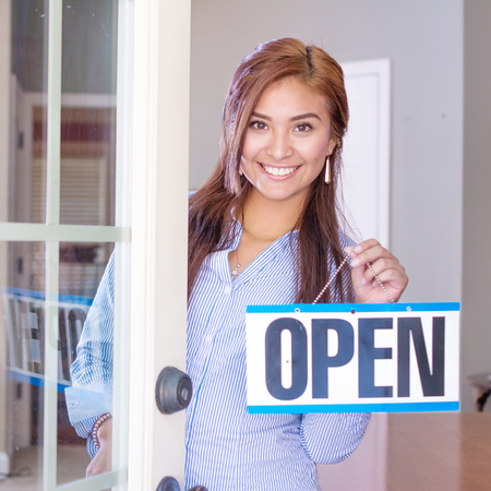 Photo pour Woman opening her store with an open sign - image libre de droit