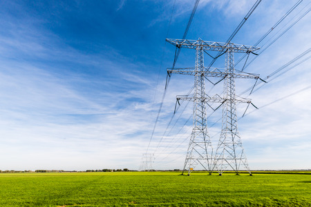 Photo pour High voltage lines and power pylons in a flat and green agricultural landscape on a sunny day with cirrus clouds in the blue sky. - image libre de droit