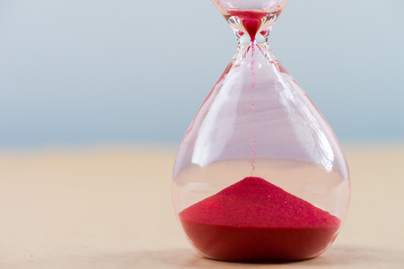 Foto de Hourglass with flowing sand on table. Time management - Imagen libre de derechos